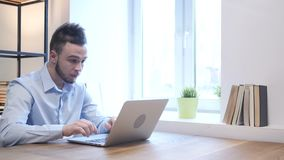 Young Man Upset by Loss while Working on Laptop. Young creative designer , good looking stock footage