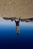 Young man upside down pushing the world Stock Photo