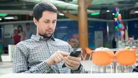 A young man use his smartphone in a shopping center mall. stock video footage