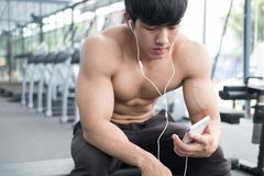 Young man use mobile phone in fitness center. male athlete liste. N to music in cellphone in gym. sporty asian guy resting in health club after working out Royalty Free Stock Photo