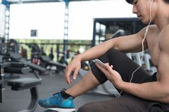 Young man use mobile phone in fitness center. male athlete liste Royalty Free Stock Photos