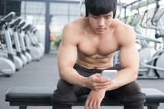 Young man use mobile phone in fitness center. male athlete liste Stock Photos