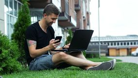 Young man use mobile phone and laptop while sitting on grass stock footage