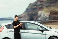 Young man use phone for network surfing or check mail white standing in front of the car with ocean rock background. Summer vocati royalty free stock photos