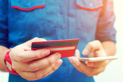 Young man use smartphone and holding credit card with shopping o Royalty Free Stock Photo