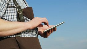 Young man uses a digital tablet. Young man uses a digital tablet on the blue sky background stock video