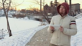A young man uses a digital tablet outdoors in winter. Portrait of a young man in a warm jacket uses a digital tablet outdoors against a background of the stock footage