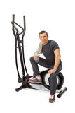 Young man uses elliptical cross trainer. Stock Image