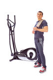 Young man uses elliptical cross trainer. Royalty Free Stock Image