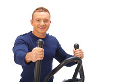 Young man uses elliptical cross trainer. Young man uses elliptical cross trainer Royalty Free Stock Photo
