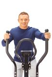 Young man uses elliptical cross trainer. Stock Photos