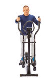 Young man uses elliptical cross trainer. Stock Images