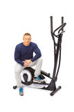 Young man uses elliptical cross trainer. Royalty Free Stock Photo