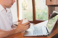 Young man uses laptop and drinking coffee or tea at his workplace Royalty Free Stock Image