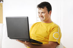 Young man uses laptop in indoor. Young man using laptop and smiling in indoor with white background Royalty Free Stock Images