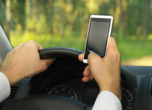Young man uses a mobile phone, driving a car royalty free stock images