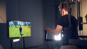 A exoskeleton with a game controls for medical use. A young man uses a modern exoskeleton with a game to control during exercise stock video