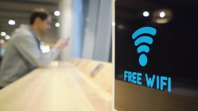 Young man uses a phone on a background of a Free Wifi Signal Sign flashes on display in a cafe.  stock video footage