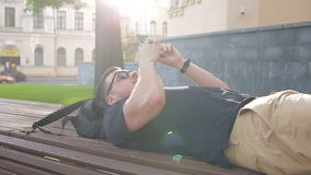 A young man uses a phone on a bench in the city stock video footage
