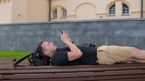 A young man uses a phone on a bench in the city stock footage