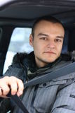 Young man uses seat belt. Young man looks friendly to a camera and shows seat belt Royalty Free Stock Photography
