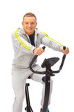 Young man uses stationary bicycle trainer. Royalty Free Stock Images