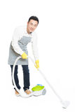 Young man uses vacuum cleaner Stock Images