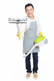 Young man uses vacuum cleaner. Chinese young man with a vacuum cleaner, white background Royalty Free Stock Photography