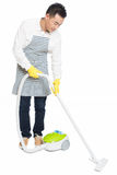Young man uses vacuum cleaner. Chinese young man with a vacuum cleaner, white background Royalty Free Stock Photo