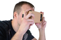 Young man uses virtual reality (VR cardboard) isolated on white background Royalty Free Stock Photos