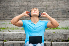 Young Man Using A Laptop And Listening Music Stock Photo