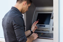 Young man using ATM Royalty Free Stock Images