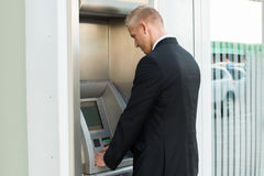 Young Man Using Atm Machine Stock Photos