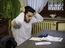 Young man using calculator and accounting at table. Handsome young man using calculator and accounting at table at home in his living room with upset, unhappy Royalty Free Stock Photo