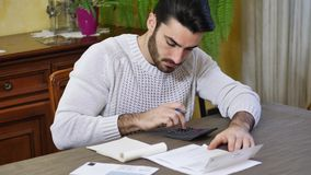 Young man using calculator and accounting at table. Handsome young man using calculator and accounting at table at home in his living room with upset, unhappy stock footage