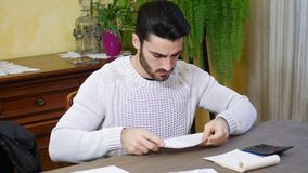 Young man using calculator and accounting at table. Handsome young man using calculator and accounting at table at home in his living room stock footage