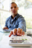 Young Man On Using Calculator At Home Stock Photo