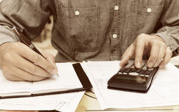 Young man using calculator and writing note in home. Stock Photography