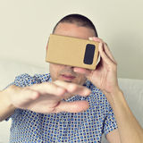 Young man using cardboard virtual reality lenses Stock Image