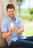 Young man using cell phone. And head phones outside Royalty Free Stock Image