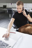 Young man using cell phone and laptop at desk in office Stock Photo