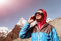 Young Man using Cell Phone in remote high Altitude Mountains sunny Royalty Free Stock Photos