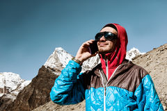 Young Man using Cell Phone in remote high Altitude Mountains toned Royalty Free Stock Image