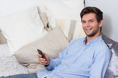Young man using cellphone on couch. Young brunette man in blue shirt using cellphone on couch Stock Photography