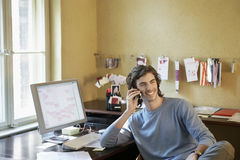 Young man Using Cellphone In Office Royalty Free Stock Photo