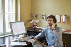 Young man Using Cellphone In Office Royalty Free Stock Images