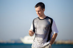 Young man using cellphone at sea stock photography