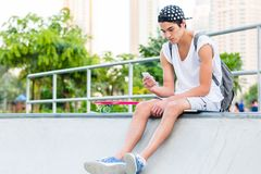 Young man using a cellphone while sitting at the skatepark. Skateboarder is sending text messages on his cell phone stock image