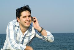 Young man using a cellular. Attractive young businessman using a cell phone at seaside against blue sky Stock Photography
