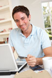 Young man using credit card on the internet Stock Image